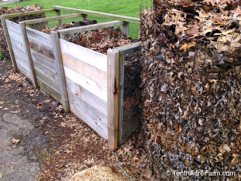 A round wire compost bin sits to the right of a wooden 3-bin unit.